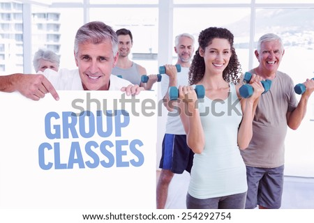 Casual man showing a poster against group classes - stock photo