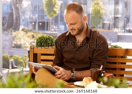 Casual man sitting in outdoor cafe on a bench, using tablet computer. - stock photo