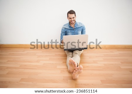 Casual man sitting on floor using laptop at home in the living room - stock photo