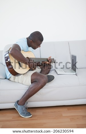Casual man sitting on sofa playing the guitar with laptop at home in the living room - stock photo