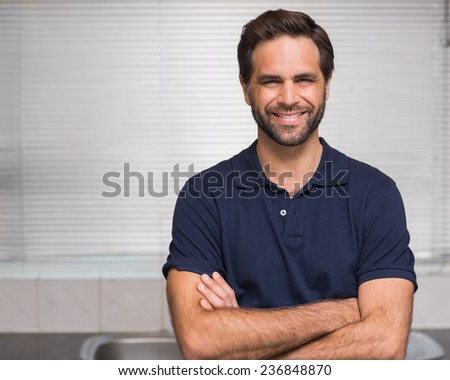 Casual man smiling at camera at home in the kitchen - stock photo