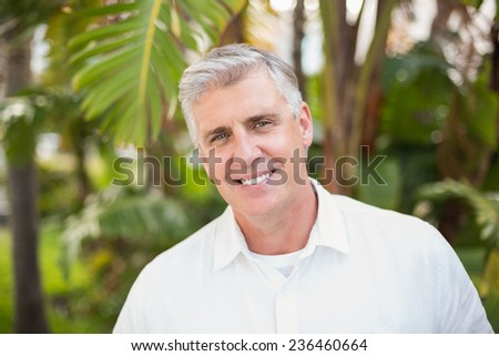 Casual man smiling at camera in a green park