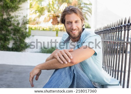 Casual man smiling at camera on a sunny day in the city - stock photo