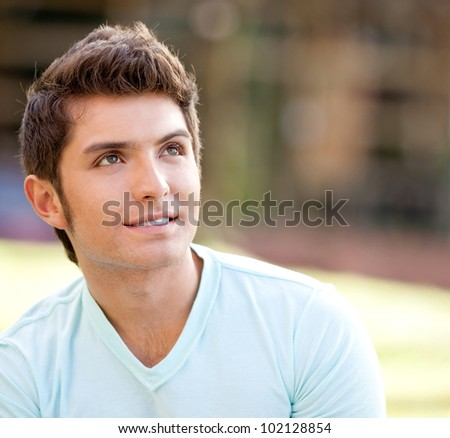 Casual man studying outdoors with a notebook