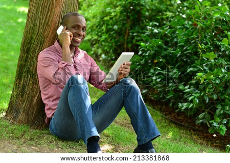 Casual man talking on the phone and holding tablet pc  - stock photo