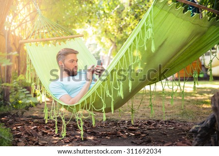 Casual man using smartphone on hammok outdoors - stock photo