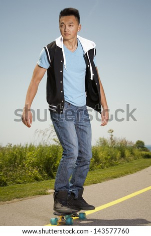 casual man wearing blue tshirt and jeans with skateboard - stock photo