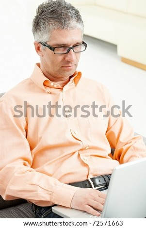 Casual man wearing jeans and orange shirt sitting on couch, working with laptop computer.?
