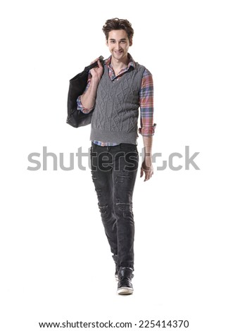 Casual Man with bag is walking towards the camera on gray background - stock photo