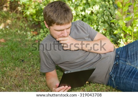 casual man working with a tablet pc, outdoor - stock photo
