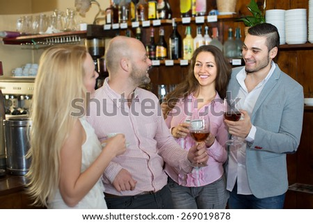 Casual meeting of smiling happy young adults at bar. Selective focus