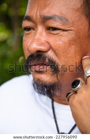 Casual middle aged man with hand near the face with a concerned look - stock photo
