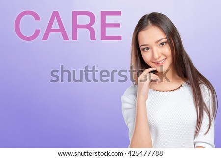 "Casual mixed-race Asian Caucasian woman near ""Care"" inscription - stock photo"