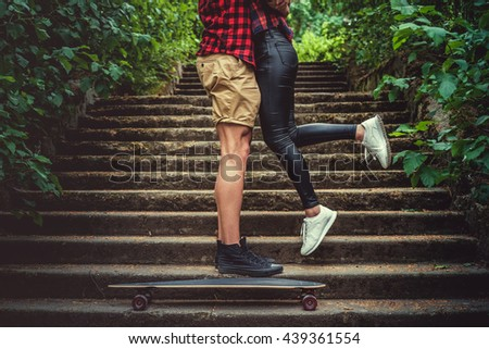 Casual moder young skateboarders couple posing on footway in a forest park. - stock photo