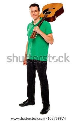 Casual music lover carrying guitar on his shoulders, full length portrait - stock photo