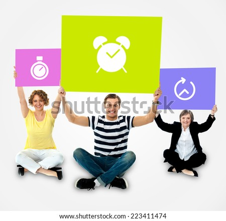 Casual people sitting and holding banner with clock sign - stock photo