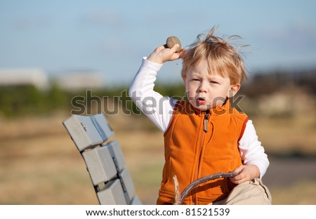 Casual portrait of a cute toddler aiming at something with a stone - stock photo