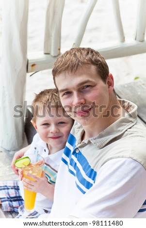 Casual portrait of a handsome young father with his son on the stairs of a beach cafe - stock photo