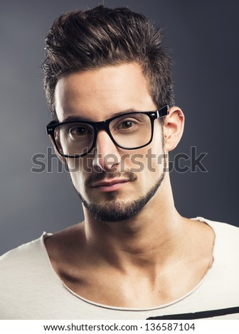 Casual portrait of a hansome young man wearing glasses, looking to the camera - stock photo