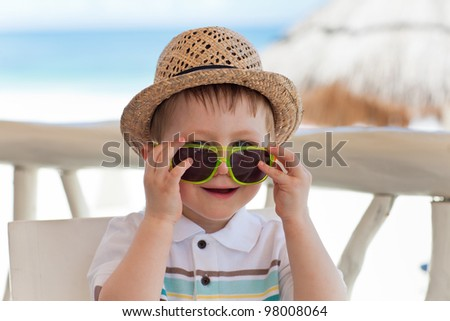 Casual portrait of a toddler boy in bright sunglasses - stock photo