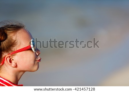Casual portrait of adorable little girl in sun glasses making funny face - stock photo