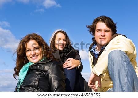 Casual portrait of three young adults on a beautiful, sunny, autumn afternoon - stock photo