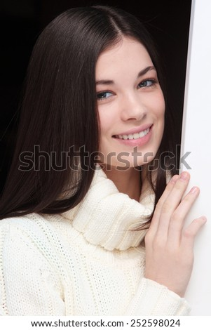 Casual portrait of young beautiful smiling girl in white pullover - stock photo
