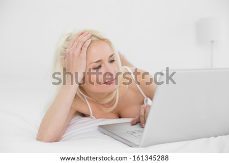 Casual relaxed young blond using laptop in bed at home