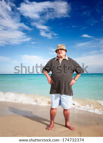 Casual senior man doing exercise on beach