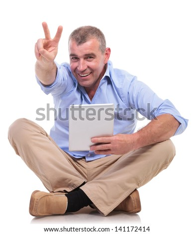 casual senior man sitting on the floor with his legs crossed and holds his tablet while showing victory sign with a smile for the camera. isolated on white background - stock photo