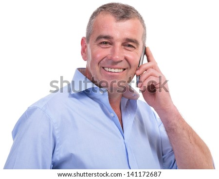 casual senior man talking on the phone while smiling for the camera. isolated on white background