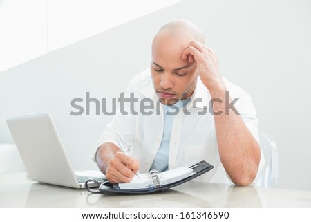 Casual serious young man with laptop writing in diary at home - stock photo