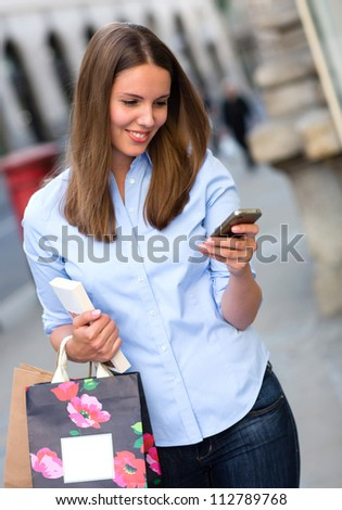 Casual shopping woman sending a text message from her phone - stock photo