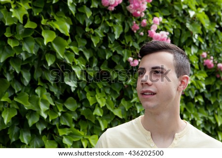 Casual sixteen year old teenage boy smiling outside - stock photo