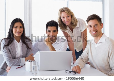 Casual smiling business team having a meeting using laptop in the office - stock photo