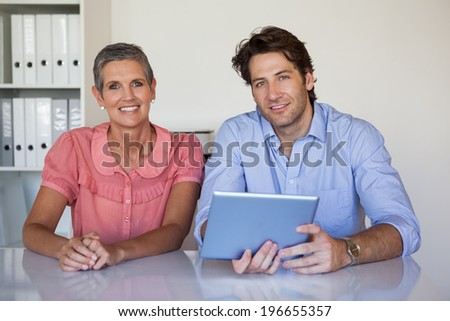 Casual smiling business team working at desk using tablet in the office