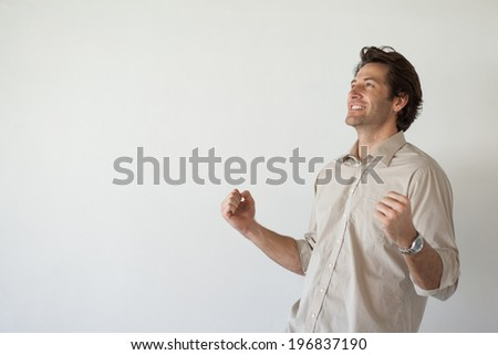 Casual smiling businessman cheering with fists clenched in his office - stock photo