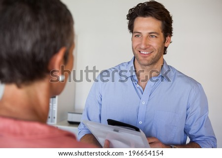 Casual smiling businessman looking at colleague in the office - stock photo