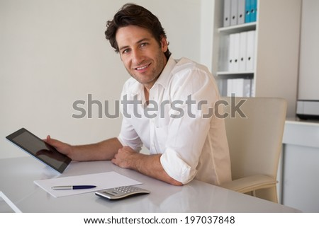 Casual smiling businessman using tablet and calculator in his office - stock photo