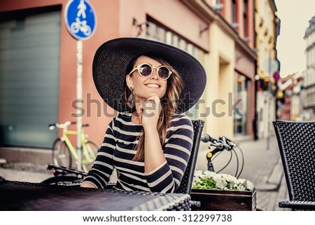 Casual smiling  lady in sunglasses and in dress with stripes sitting at the table on the street in old town. - stock photo