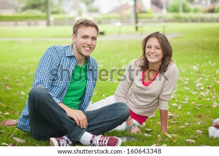 Casual smiling students sitting on the grass on campus at college
