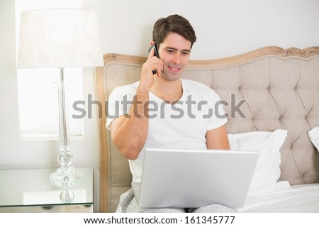 Casual smiling young man using cellphone and laptop in bed at home