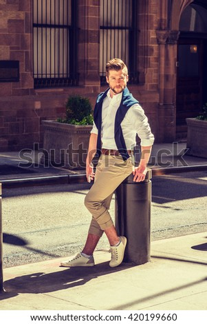 Casual Spring Fashion in New York. American Man with beard wearing white shirt, tan pants, sneakers, blue sweater putted around shoulder, holding cell phone, sitting on street with vintage building.  - stock photo