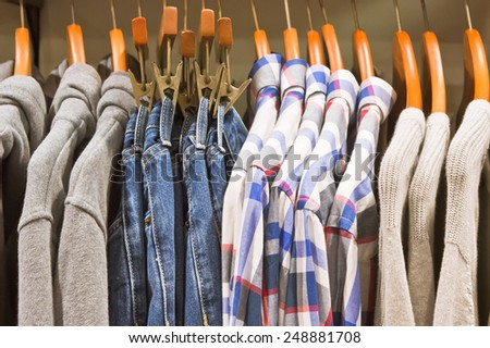 Casual sweaters trousers and shirts hanging in a store - stock photo