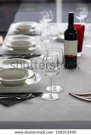 Casual table setting with cutlery, plates and wine glasses - stock photo