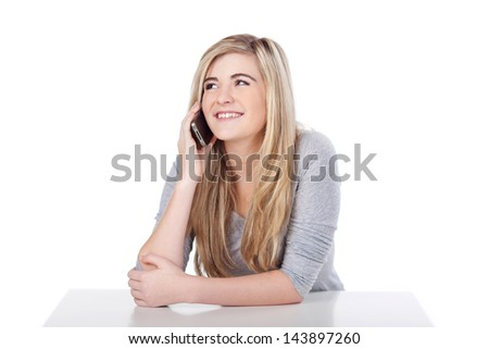 Casual teenage girl using mobile phone against white background - stock photo