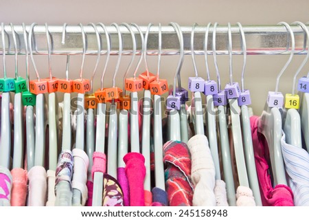 Casual tops on hangers in a charity store - stock photo