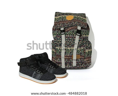 Casual trendy flat hi-cut pair of shoes and patterned bag on white background