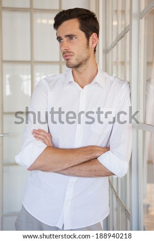 Casual upset businessman leaning against window in his office