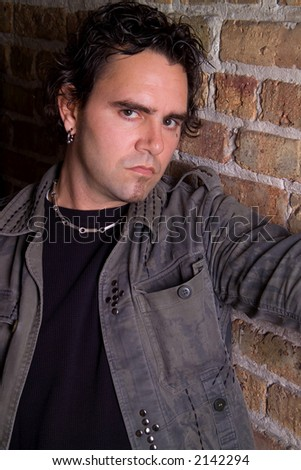 Casual urban headshot of man on brick wall - stock photo